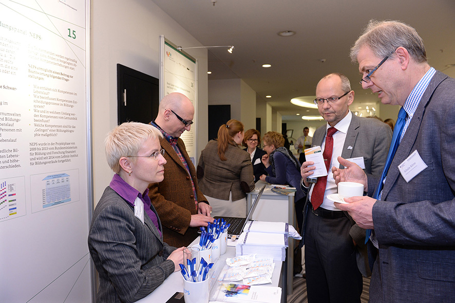 "Director of LIfBi, Hans-Günther Roßbach, and Executive Director of Research, Jutta von Maurice, in conversation with the Director of the Clinic and Polyclinic for Children and Adolescent Psychiatry, Psychosomatics, and Psychotherapy of LMU Munich, Gerd Schulte-Körne, at the NEPS convention booth on the ""market square""."